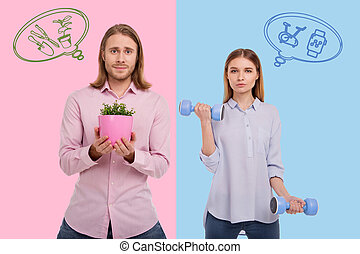 Smiling man standing with a flowerpot while his wife holding hand weights