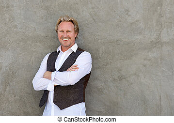 smiling man standing with arms crossed against a wall