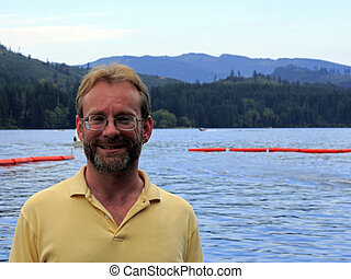 Smiling Man - Middle aged male standing in front of a lake...