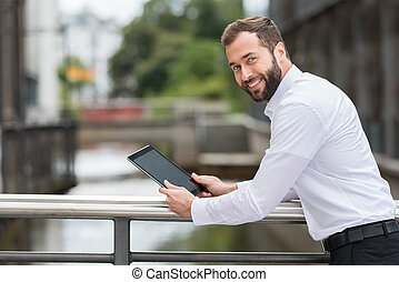 Smiling man surfing the web on his tablet