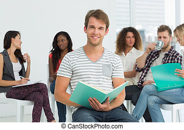 Smiling man taking notes while colleagues are talking behind him in creative office