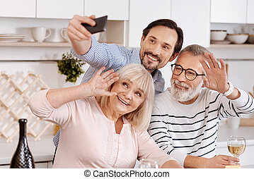 Smiling man taking selfie with senior parents at home