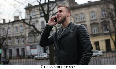 Smiling man talking on his phone while standing in the street.