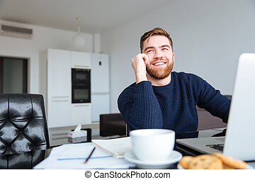 Smiling man talking on the phone at home