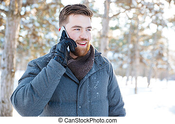 Smiling man talking on the phone in winter park