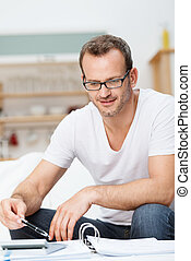 Smiling man totalling up his accounts - Smiling good looking...