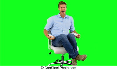 Smiling man turning on swivel chair on green screen in slow...