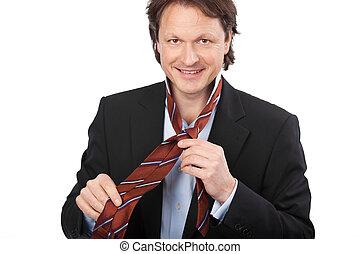 Smiling man tying his tie