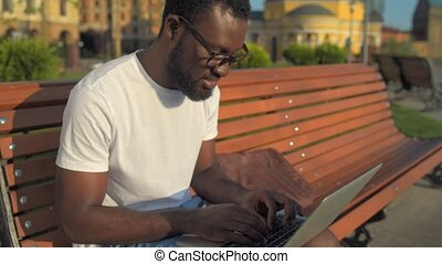 Smiling man typing while working on a laptop in park -...