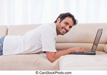 Smiling man using a notebook