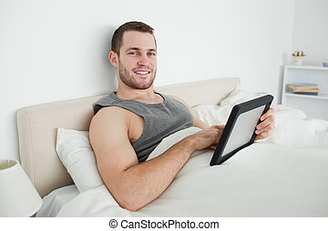 Smiling man using a tablet computer