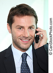 Smiling man using a telephone