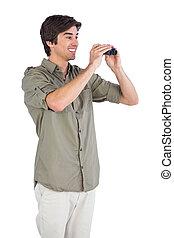 Smiling man using binoculars