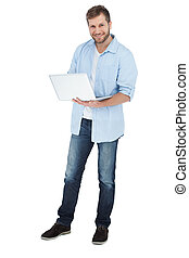 Smiling man using his laptop looking at camera