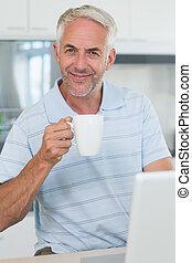 Smiling man using his laptop while