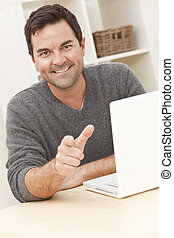 Smiling Man Using Laptop Computer At Home Pointing To Camera