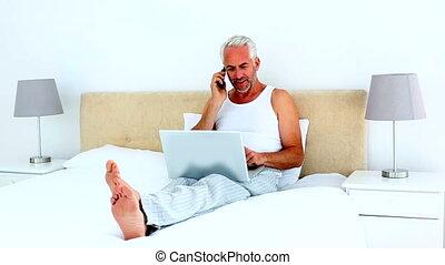 Smiling man using laptop while on t
