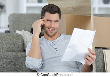 smiling man using mobile phone near paper at home