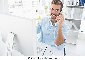 Smiling man using phone and computer in office