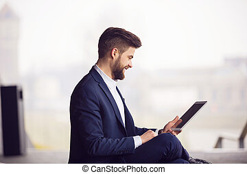 Smiling man using tablet