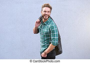 Smiling man walking looking over shoulder