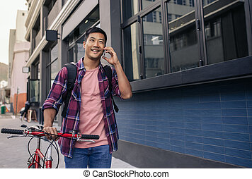 25012db83 Smiling man walking with his bike talking on a cellphone. Smiling young  Asian man in a plaid shirt ...