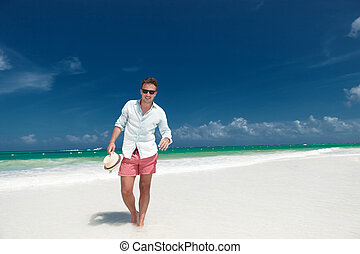 smiling man walks on the beach with hat in hand