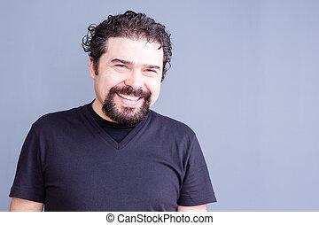 Smiling Man Wearing Black T-Shirt in Gray Studio