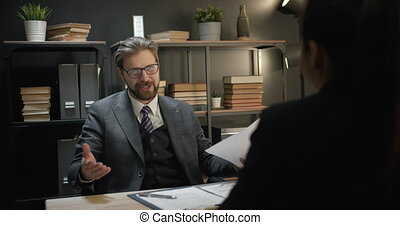 Smiling bearded man in trendy suit sitting at own office and welcoming new female worker at team after successful interview. Formal greeting with handshaking. Employment concept.