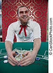 Smiling Man Wins Big at Blackjack - A man wearing glasses, a...
