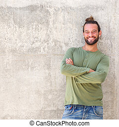 Smiling man with arms crossed leaning against wall