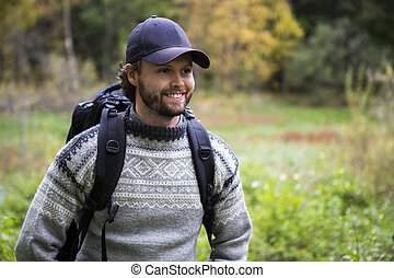 Smiling Man With Backpack Hiking In Forest