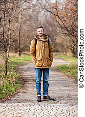 Smiling man with backpack standing outdoors