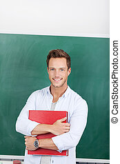 Smiling Man With Folder In Front Of Chalkboard