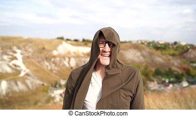 Smiling man with glasses in t-shirt and cape walks in hilly terrain. Close up of adult laughing male in hood being blown by wind