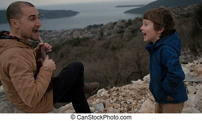 Smiling man with guitar and boy on edge of cliff.