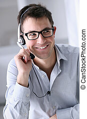 smiling man with headphones in office, call center