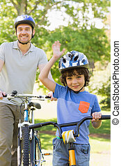 Smiling man with his son riding bicycles
