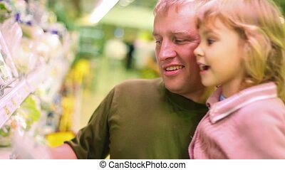 smiling man with little girl buying parsley in supermarket