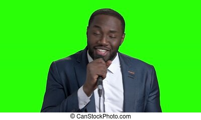Smiling man with microphone on green screen. The...