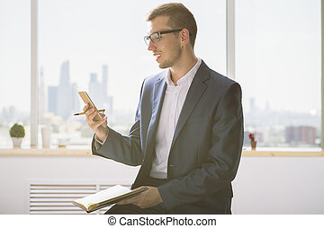 Smiling man with notepad using smartphone