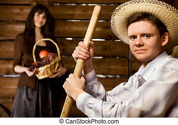 smiling man with pitchfork and in straw hat sitting on bench in wooden log hut, young woman with basket of fruit standing near wall on background, close up