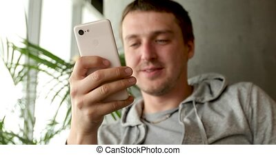 Smiling man with smartphone in hand sitting in cafe