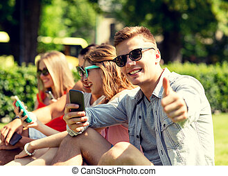 smiling man with smartphone showing thumbs up - friendship, ...