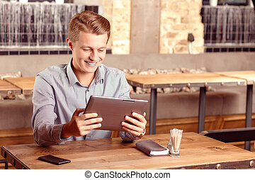 Smiling man with tablet in cafe