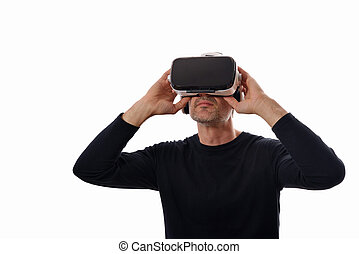 Smiling man wearing black pullover and virtual reality glasses holding glasses looking up. Isolated white