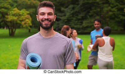 smiling man with yoga mat over group of people - fitness, ...