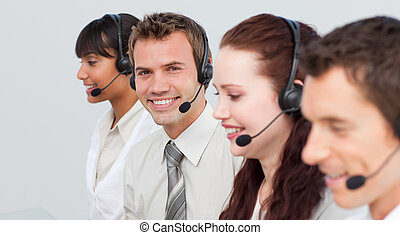 Smiling man working in a call center with his colleagues