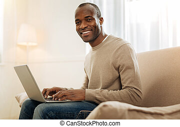 Smiling man working on the laptop