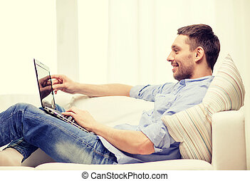 smiling man working with laptop at home - technology, home...